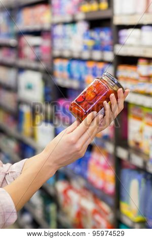 A pretty woman showing a jar in a supermarket