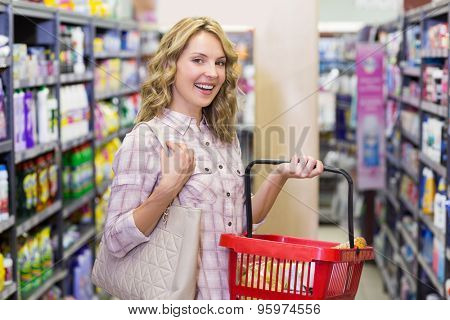 Portrait of a smiling pretty blonde woman buying a products with a shopping basket in supermarket