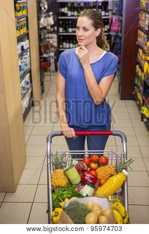 Thoughtful pretty woman pushing trolley in aisle at supermarket