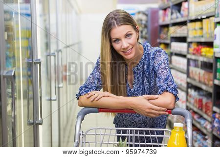 Portrait of smiling woman walking with his trolley on aisle at supermarket