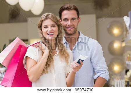 Portrait of a happy couple looking at beauty product at the mall