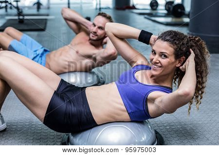 Portrait of a muscular couple doing bosu ball exercises