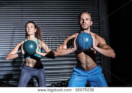 Muscular couple doing ball exercise at the crossfit gym