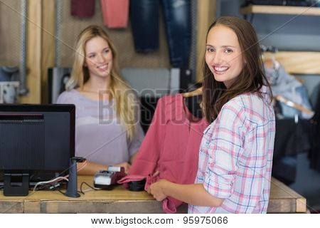 Pretty brunette doing shopping and smiling at camera in clothes store