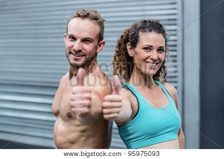 Back to back muscular couple gesturing thumbs up