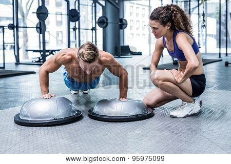 Trainer watching muscular man doing bosu ball push ups