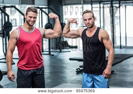 Portrait of two muscular men flexing biceps