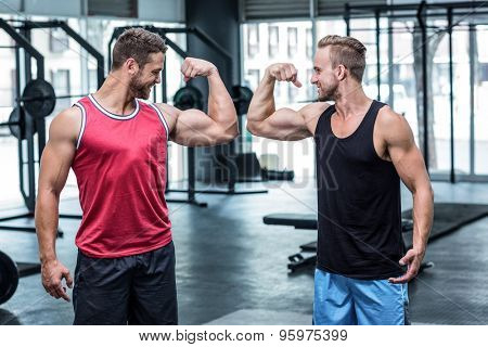 Portrait of two smiling muscular men flexing biceps