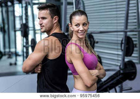 Muscular couple giving back to back with arm crossed