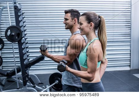 Side view of a muscular couple lifting dumbbells