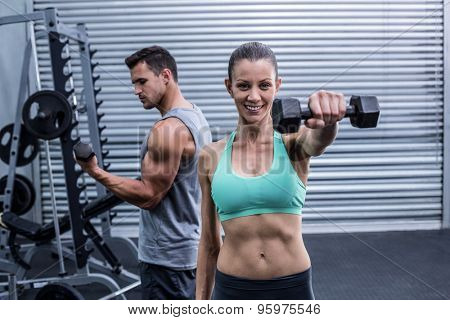 Portrait of a muscular woman lifting dumbbells