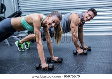 Portrait of muscular couple doing plank exercise together