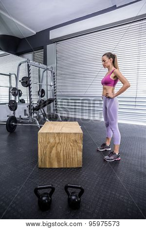 Standing muscular woman resting herself at the crossfit gym