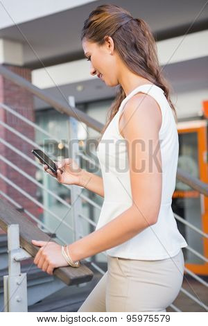 Smiling woman going upstairs while using her smartphone at the shopping mall
