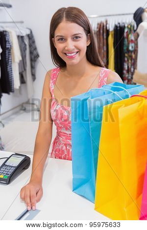 Portrait of smiling woman paying by credit card at a boutique