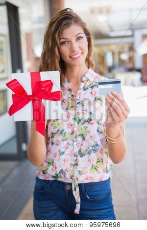 Portrait of smiling woman showing gift box and credit card to the camera at the shopping mall