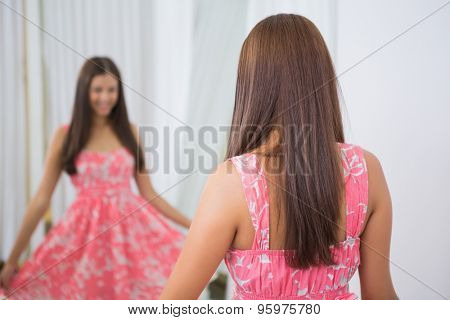 Smiling woman trying on a dress at a boutique