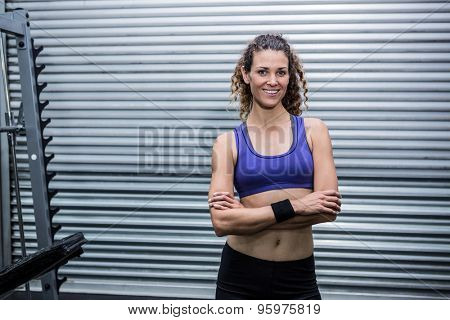 Portrait of muscular woman with arms crossed in crossfit gym