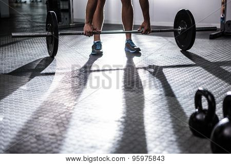 Muscular man lifting a barbell in crossfit gym