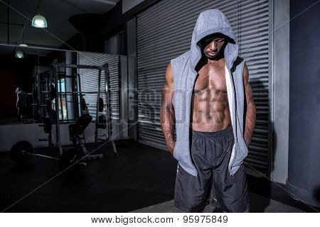 Young Bodybuilder in a hoodie looking at the hoodie in the crossfit gym