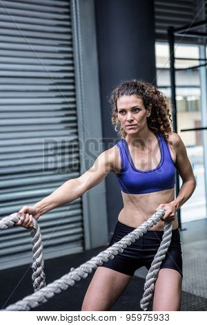 Muscular woman exercising with rope in crossfit gym