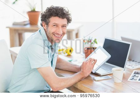 Casual designer using graphics tablet and laptop in the office
