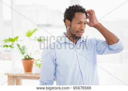 Young thinking businessman scratching his head in the office