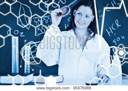 Science graphic against pretty scientist looking at a petri dish