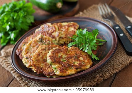 Zucchini pancakes with parsley on a wooden table.