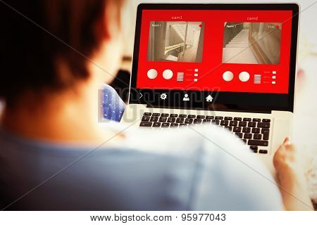 Pregnant woman using her laptop against home control system