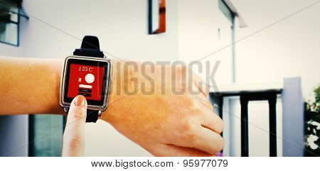 Smartwatch on wrist against home control centre