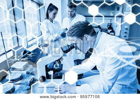 Science graphic against scientist looking through a microscope