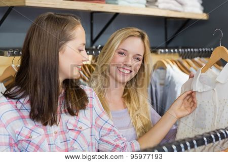 Smiling blonde woman showing clothes to her friend in clothes store