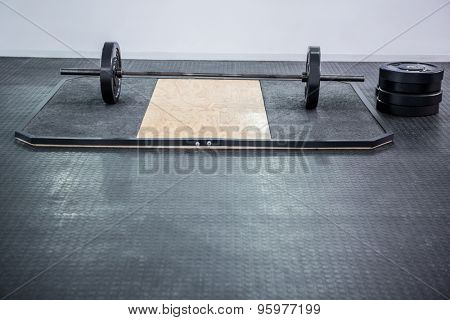 A barbell next to weights in crossfit gym