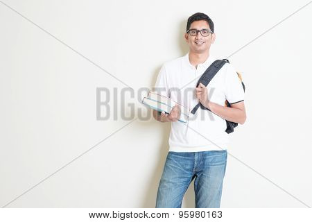 Portrait of adult Indian university student with books and bag. Asian man standing on plain background with shadow and copy space. Handsome mixed race male model.