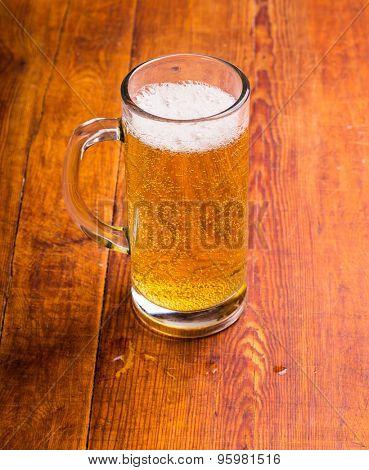 Mug of beer on wooden background.