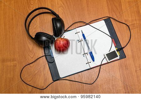 Headphones, Music Player, Pen And Apple Lie On Notebook. School.