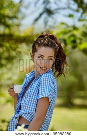 Woman drinking morning coffee in the garden