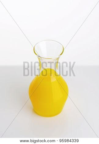 carafe of fresh orange juice on white background