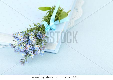 Forget-me-nots flowers on book, on blue background