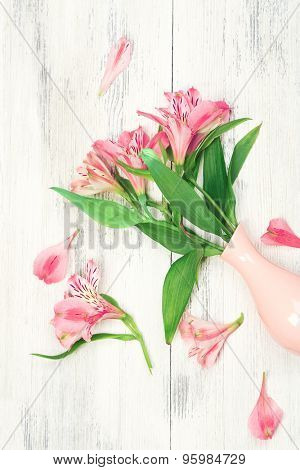 Beautiful alstroemeria in vase on wooden background