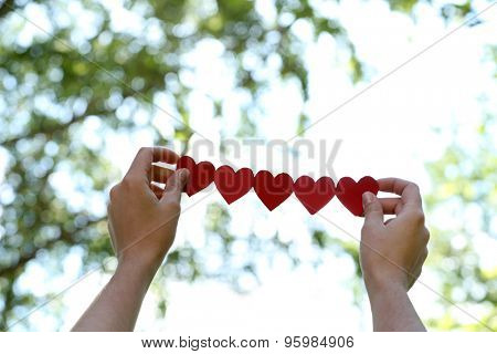 Female hands with chain of paper hearts over nature background