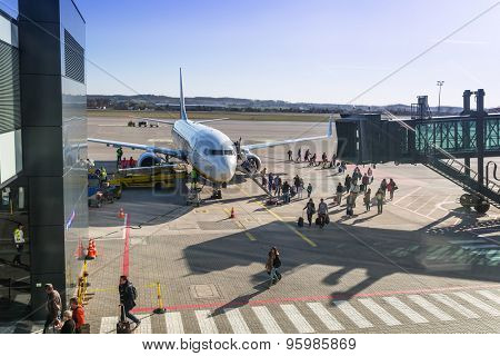 GDANSK AIRPORT, POLAND - 10 APRIL 2015: People boarding to Ryanair plane on Lech Walesa Airport in Gdansk. Ryanair operates over 300 aircraft and is the biggest low-cost airline company in Europe.