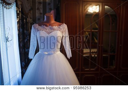 White wedding dress hanging on a mannequin in a room inside the