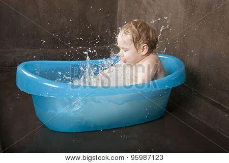 Blonde Baby Splashing In Blue Little Bath Indoor