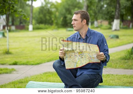 Young male tourist with map in hand looking around. Tourist map of the city of Moscow, Russia