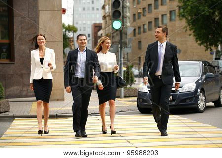 Full length portrait of a young four successful business people crossing the street in the city center