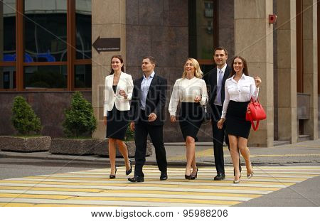 Successful Team of five business people confidently striding along the summer street