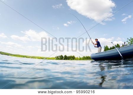 Young man fishing on the fresh water pond at sunny day