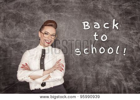 Happy Teacher On The School Blackboard Background